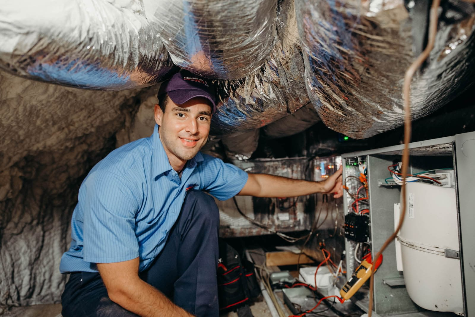 hvac technician repairing furnace