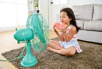 Small female child sitting in front of electric fan blowing cooling wind and eating cold watermelon feeling refreshing during summer season.