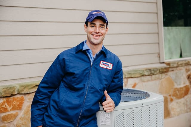 hvac technician leaning on outdoor unit