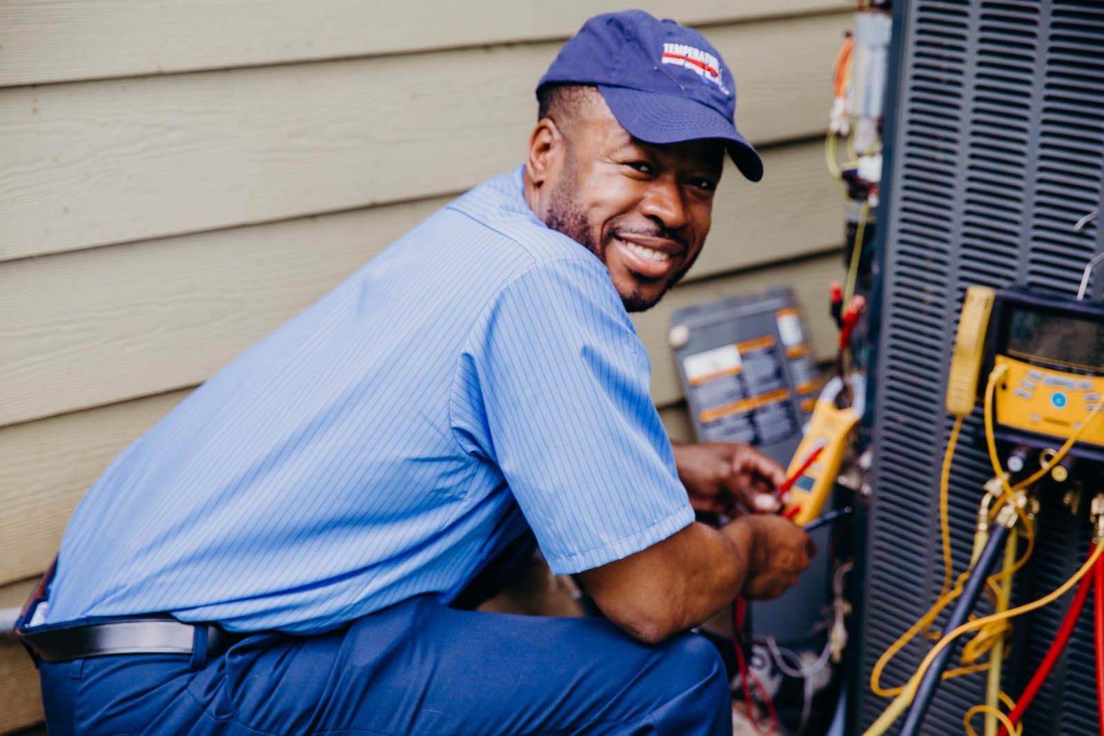 hvac technician working on outdoor heating and cooling unit