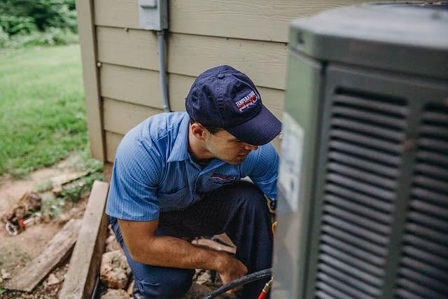 hvac technician servicing an outdoor unit