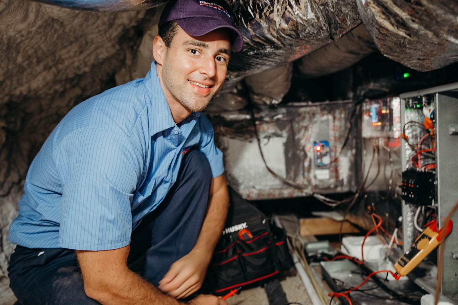 hvac technician maintaining an attic air conditioning system