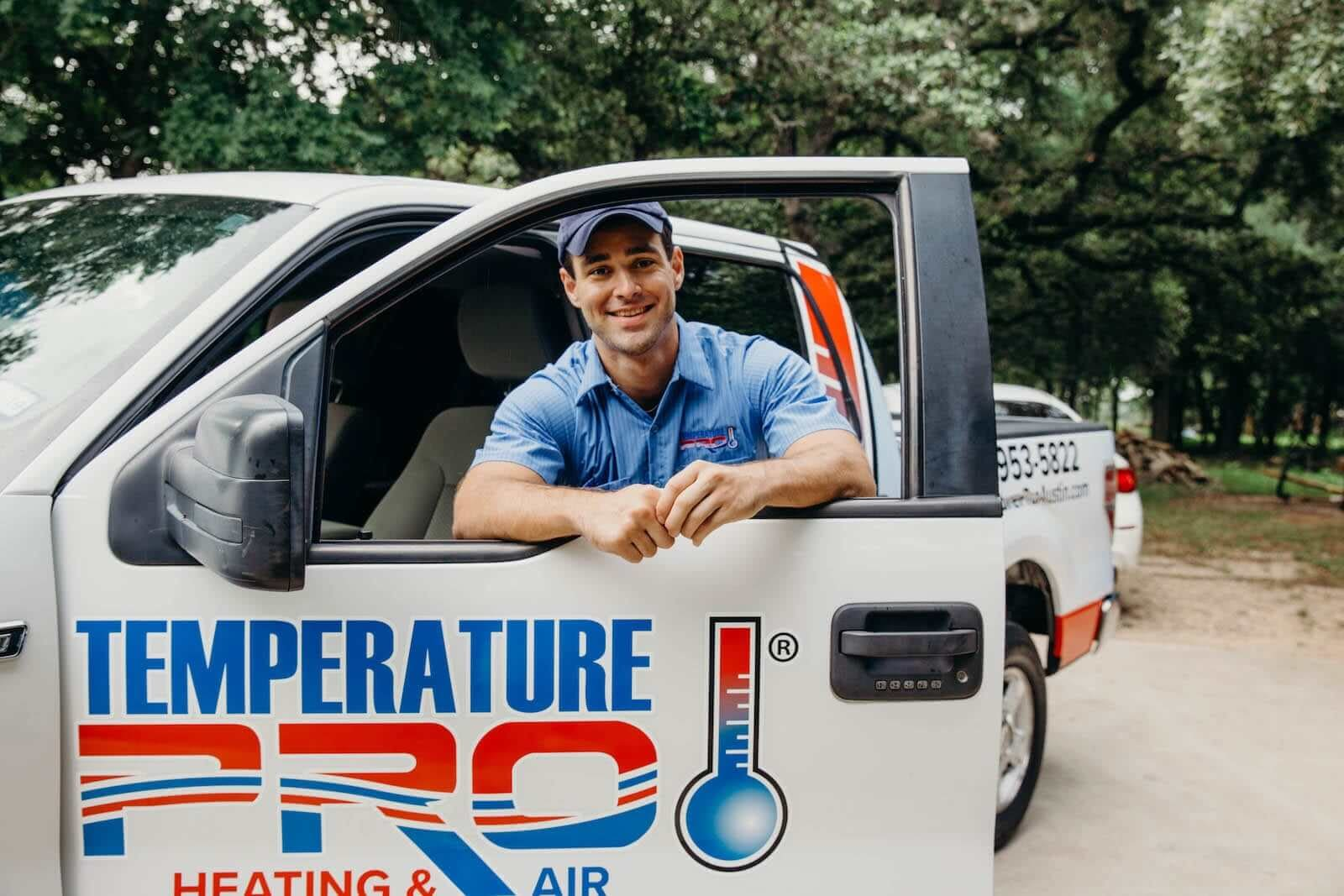 hvac technician standing with his truck