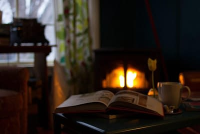 open book sitting in front of a fireplace