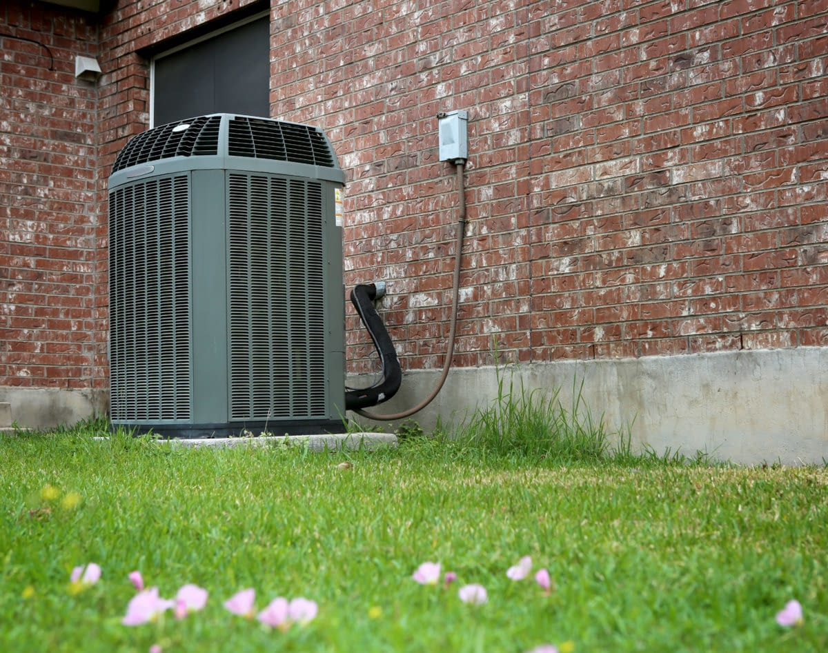 residential air conditioning unit outside of a brick home