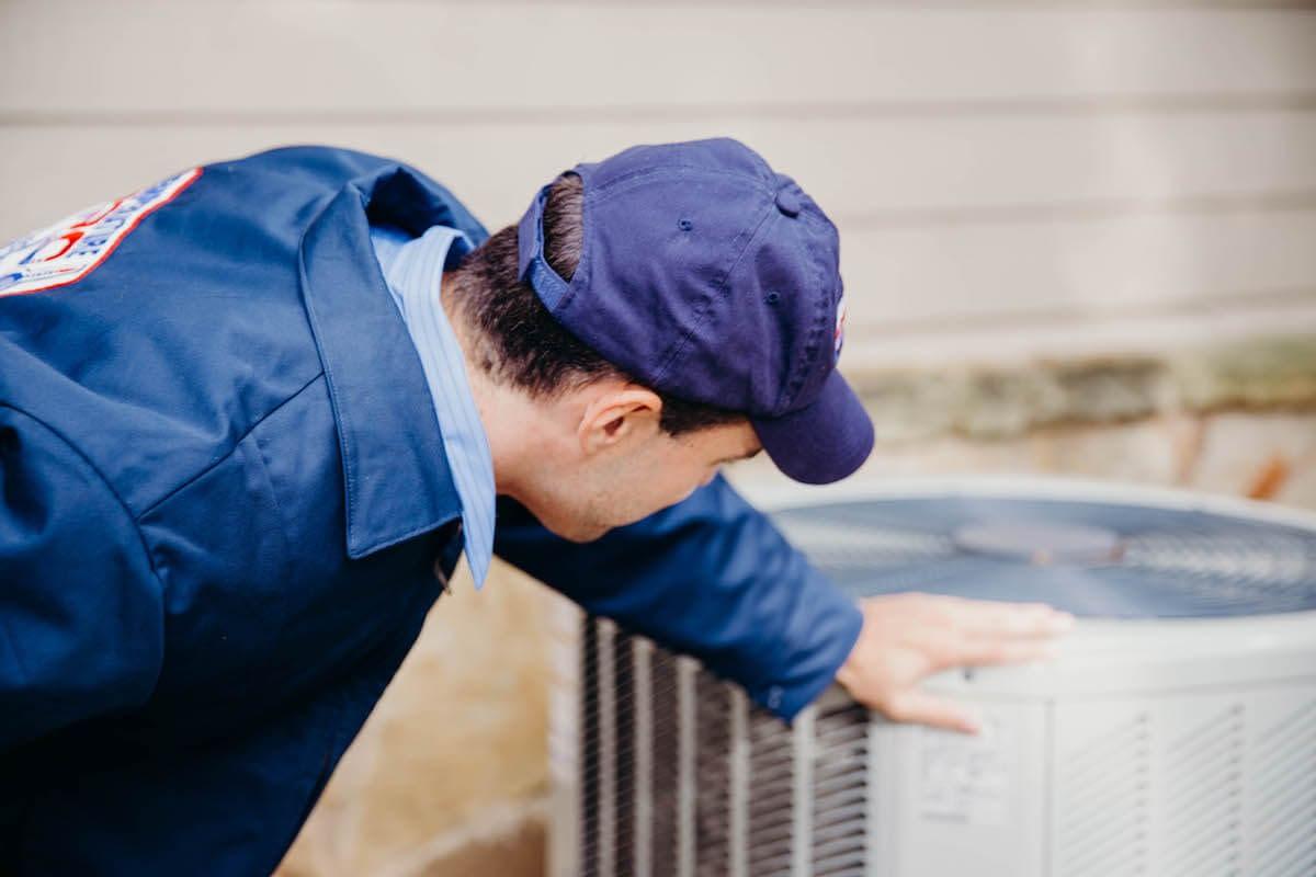 hvac technician inspecting furnace